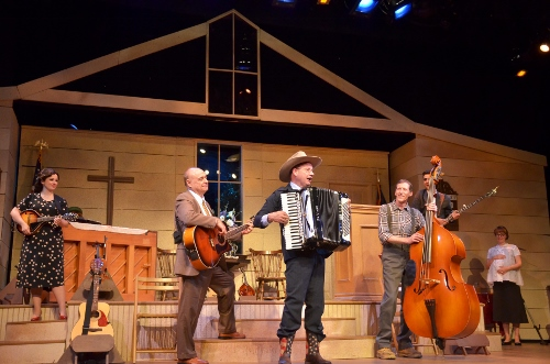 Sporting his new boots and cowboy hat, the Rev. Mervin Oglethorpe (John Vessels), center, sings 'Roundup in the Sky' with the Singing Sanders Family (from left), Denise Sanders Culpepper (Christina Rose Rahn), Burl Sanders (Bob Payne), Dennis Sanders (Brian Gunter), Dennis Sanders (Will Boyajian) and June Sanders Oglethorpe (Sarah Hund) in Beef & Boards Dinner Theatre's production of Smoke on the Mountain: Homecoming. This sequel in the popular bluegrass gospel series is on stage through Aug. 16. Tickets include Chef Odell Ward's dinner buffet.