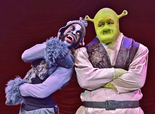 Donkey (Julius Thomas III) leaps into the arms of the ogre Shrek (Peter Scharbrough) in Beef & Boards Dinner Theatre's premiere production of 'Shrek, The Musical.'