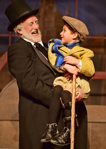 Ebenezer Scrooge (Jeff Stockberger), left, lifts Tiny Tim (Ashton Curry) in Beef & Boards Dinner Theatre's one-hour production of 'A Christmas Carol'.