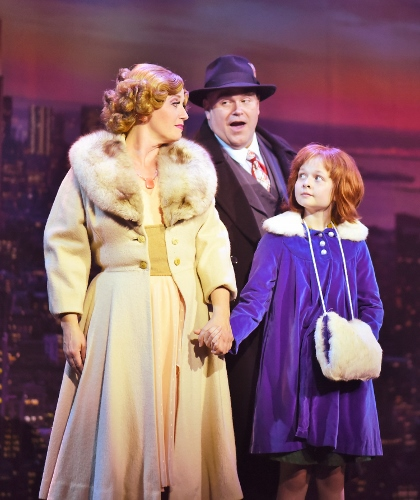 "NYC: Oliver Warbucks (Ty Stover), center, sings about ""NYC"" to Grace (Bobbi Bates), left, and Annie (Claire Kauffman), right, during the child's first night out on the town in Beef & Boards Dinner Theatre's production of Annie, now on stage through July 15."
