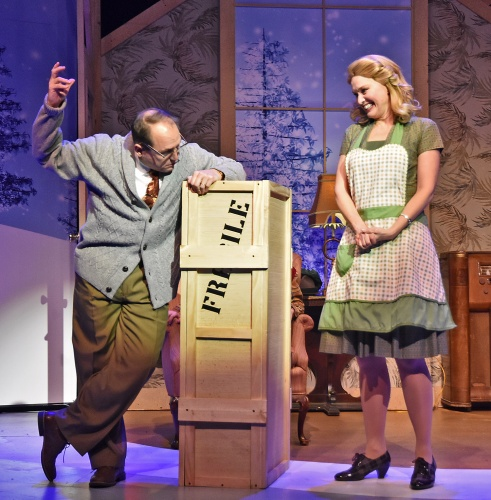 "Sounding out the word on the size of the wooden crate that contains his unknown crossword puzzle prize, The Old Man (Don Farrell), left, sounds out ""fra-gee-lay,"" and determines it must be ""Italian"" as Mother (Amy Bodnar) smiles in Beef & Boards Dinner Theatre's production of 'A Christmas Story: The Musical.'"