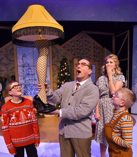 The Old Man (Don Farrell) proudly holds up his crossword puzzle prize as Mother (Amy Bodnar) watches in dismay and his sons Ralphie (Ben Kistner), left, and Randy (Fender Brokamp), right, watch in awe in Beef & Boards Dinner Theatre's production of 'A Christmas Story: The Musical'.