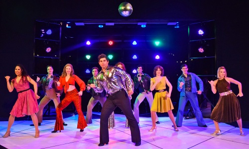 "Tony Manero (Jeremy Sartin), center, dances to ""You Should Be Dancing"" at the 2001 Odyssey Club in Saturday Night Fever, now on stage at Beef & Boards Dinner Theatre. This disco-mania musical is based on the famous film, and is on stage through March 29."