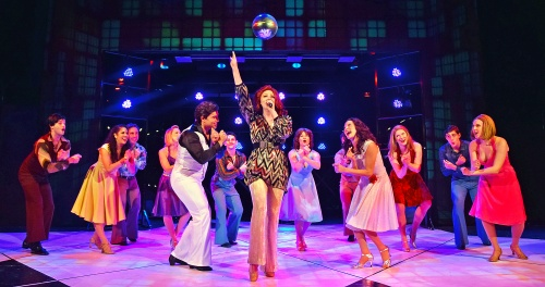 "Candy (Megan Flynn), center, sings ""Night Fever"" at the 2001 Odyssey Club in Saturday Night Fever, now on stage at Beef & Boards Dinner Theatre. This disco-mania musical is based on the famous film, and is on stage through March 29."