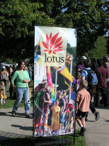People walk past Lotus sign during the free festival afternoon: Lotus in the Park