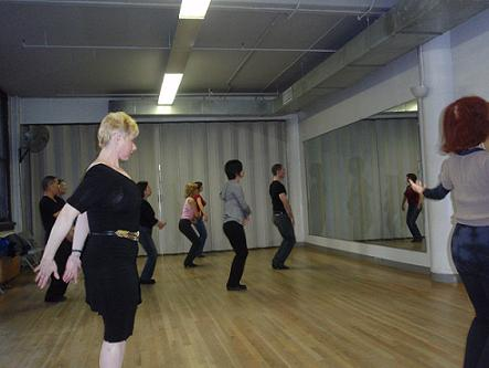 Students in Jules Helm's Advanced Cha Cha class, during warm-up. Mr. Helm (in jeans and black t-shirt) leads the class.